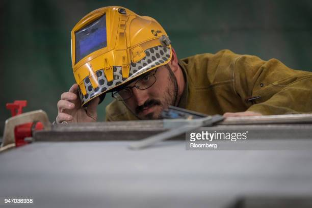 A worker uses a square to measure the side of a door during production at the Metal Manufacturing Co facility in Sacramento California US on Thursday...