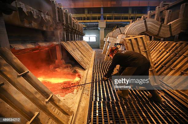 A worker uses a tool to move molten aluminum in the electrolysis bath inside the electrolysis shop at the Irkutsk aluminium smelter operated by...