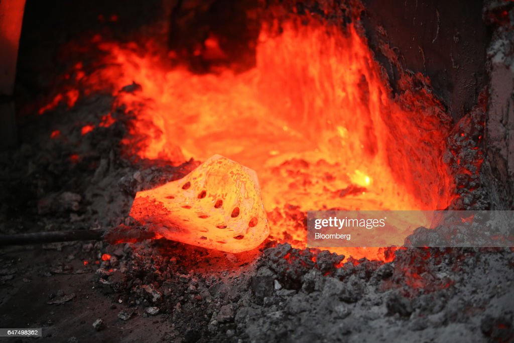 A worker uses a tool to move molten aluminum in the
