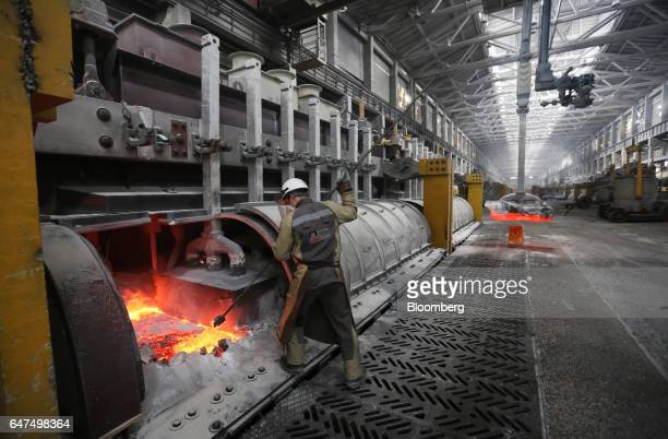A worker uses a tool to move molten aluminum in the electrolysis bath inside the electrolysis shop at the Krasnoyarsk aluminum smelter operated by...