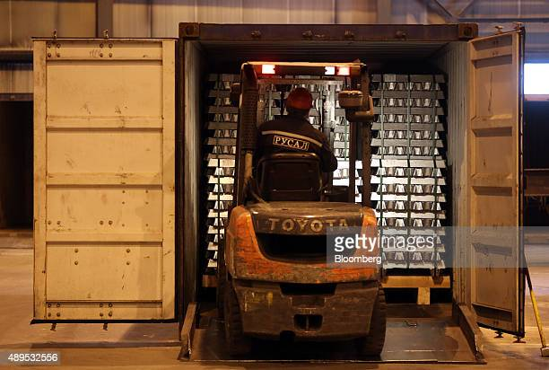 A worker uses a Toyota Motor Corp forklift truck to load stacks of aluminum ingots into a shipping container for distribution at the Irkutsk...
