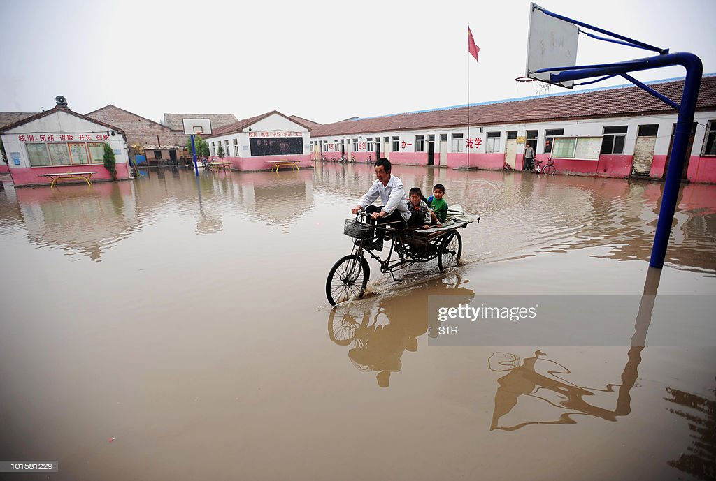 A worker uses a tricycle to ferry students to their classrooms across a flooded school yard after heavy rains in a suburb of Beijing on June 2, 2010. Summer rain storms annually deluge many parts of China, often with devastating results leading to hundreds of fatalities. CHINA