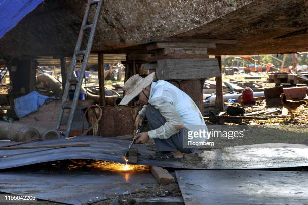 A worker uses a welding torch while working on a fishing boat at a shipbuilding company in Quang Nam province Vietnam on Wednesday June 26 2019...