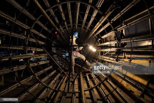 TOPSHOT A worker uses an acetylene torch to cut through metal bars at a construction site in Manila on October 13 2018