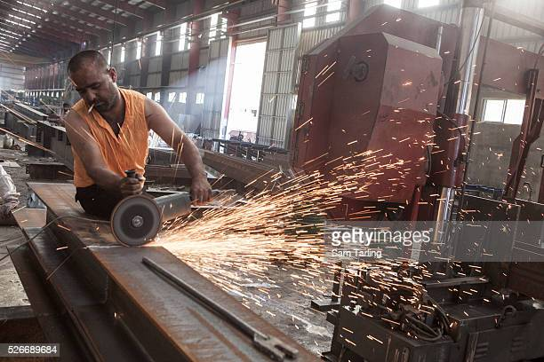 A worker uses an angle grinder at a steel factory in the Bekaa Valley Lebanon on July 19 2011