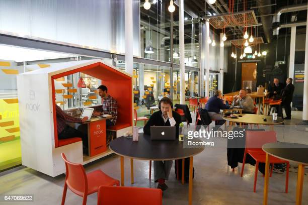 A worker uses an Apple Inc laptop in the communal area at the offices of Boxarr Ltd inside The Engine Shed in Bristol UK on Friday Feb 24 2017...