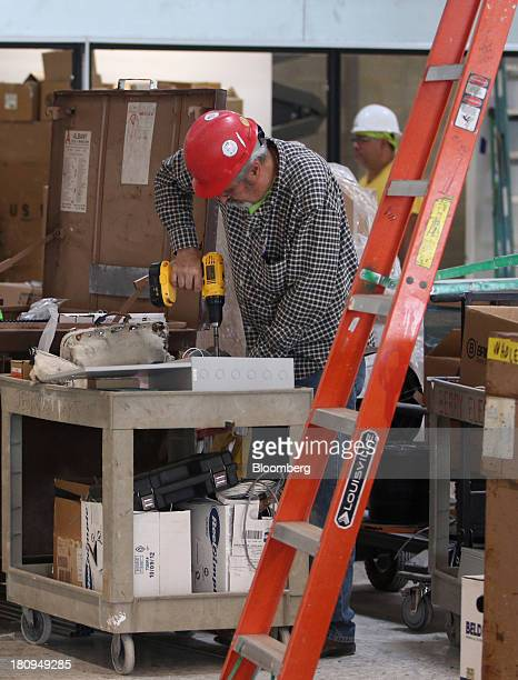 Worker uses an electric drill inside a new Whole Foods Market Inc. Store under construction in Park Ridge, Illinois, U.S., on Tuesday, Sept. 17,...