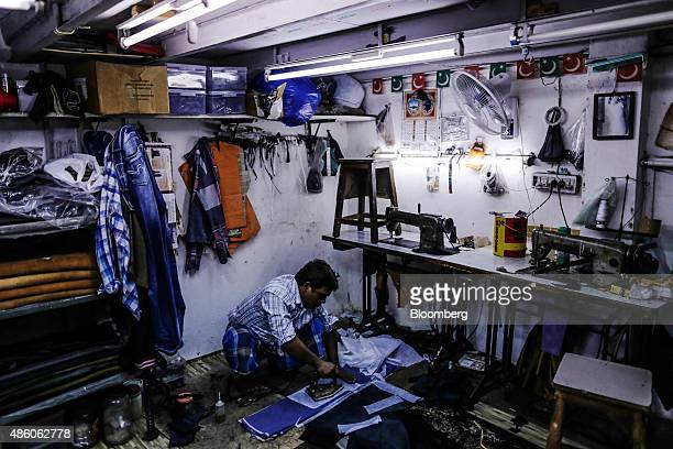 A worker uses an iron on a piece of leather for a jacket at a leather workshop in the Dharavi slum area of Mumbai India on Saturday Aug 29 2015...