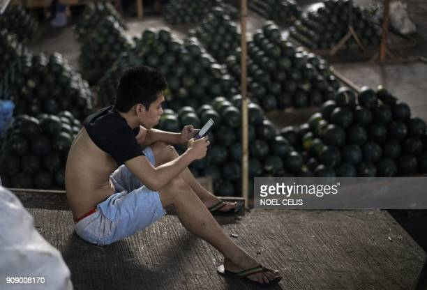 A worker uses his mobile phone during a break at a market in Manila on January 23 2018 An estimated 10 million Filipinos work overseas and the money...
