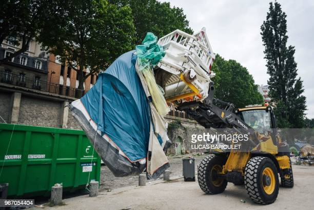 A worker usew an excavator to clean up a migrants' makeshift camp along the Canal de SaintMartin at Quai de Valmy in Paris following its evacuation...