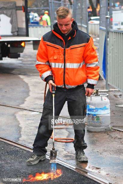 worker using a gas blow torch to heat asphalt. - foundation make up stock pictures, royalty-free photos & images