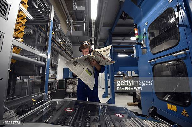 A worker using a magnifying glass controls the quality of printing on a newspaper during a test phase of the new printing rotary press at French...