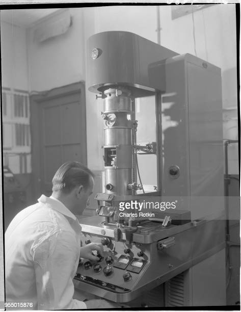 Worker using an electronic microscope A worker in the electrical division of the East Alton Works plant uses an electronic microscope for battery...