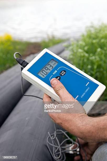 Worker Using an Ultrasonic Pipeline Flow Meter