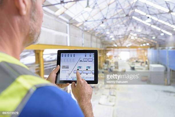 Worker using digital tablet to control robotic machinery in architectural stone factory