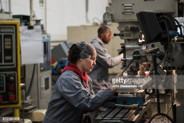 Worker using drill press in factory