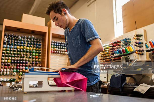 worker using embroidery machine in t-shirt  printing workshop - heshphoto stock pictures, royalty-free photos & images