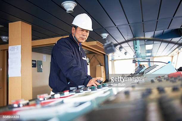 worker using equipment at shipping port, goseong-gun, south korea - dock worker stock photos and pictures