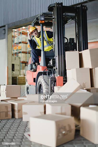 Worker using forklift to pick up boxes