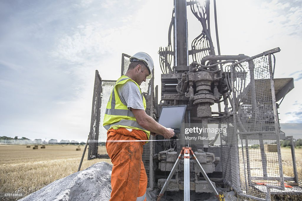 Worker using laptop to survey drilled hole made by drilling rig in field : Stock Photo