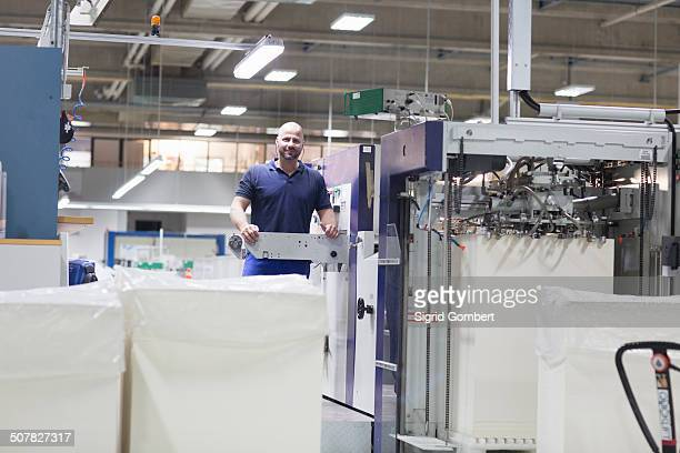 worker using machine in paper packaging factory - sigrid gombert stock pictures, royalty-free photos & images