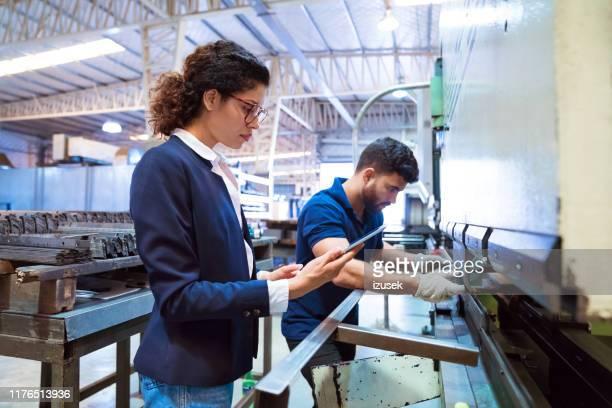 arbeiter mit maschinen von manager in der fabrik - izusek stock-fotos und bilder