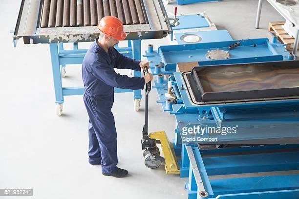worker using manual pallet jack in industrial plant - sigrid gombert stock-fotos und bilder