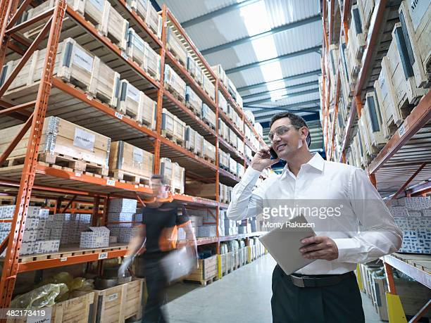 Worker using mobile phone and holding digital tablet in parts store in factory