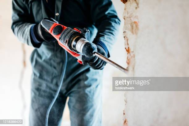 worker using pneumatic hammer drill to cut the wall concrete brick, close up - renovation stock pictures, royalty-free photos & images