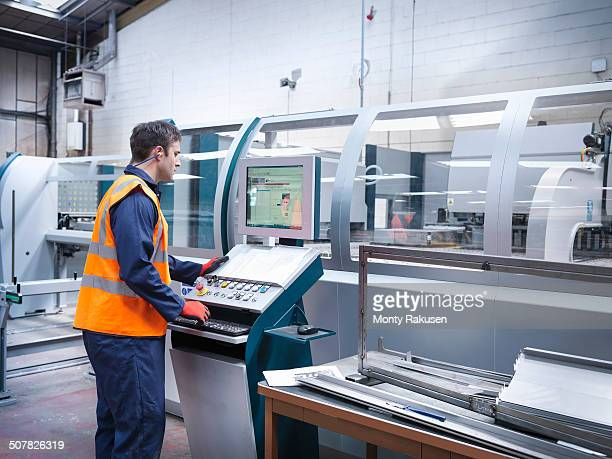 Worker using robotic metal cutting machine in sheet metal factory