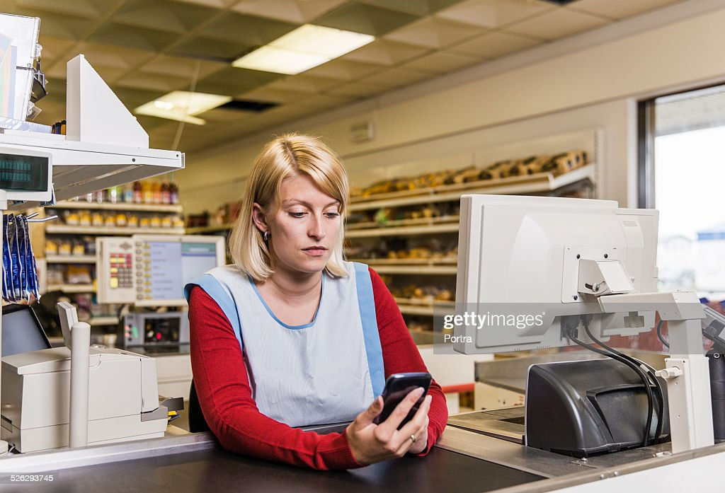 Worker using smart phone at counter in store : Stock Photo