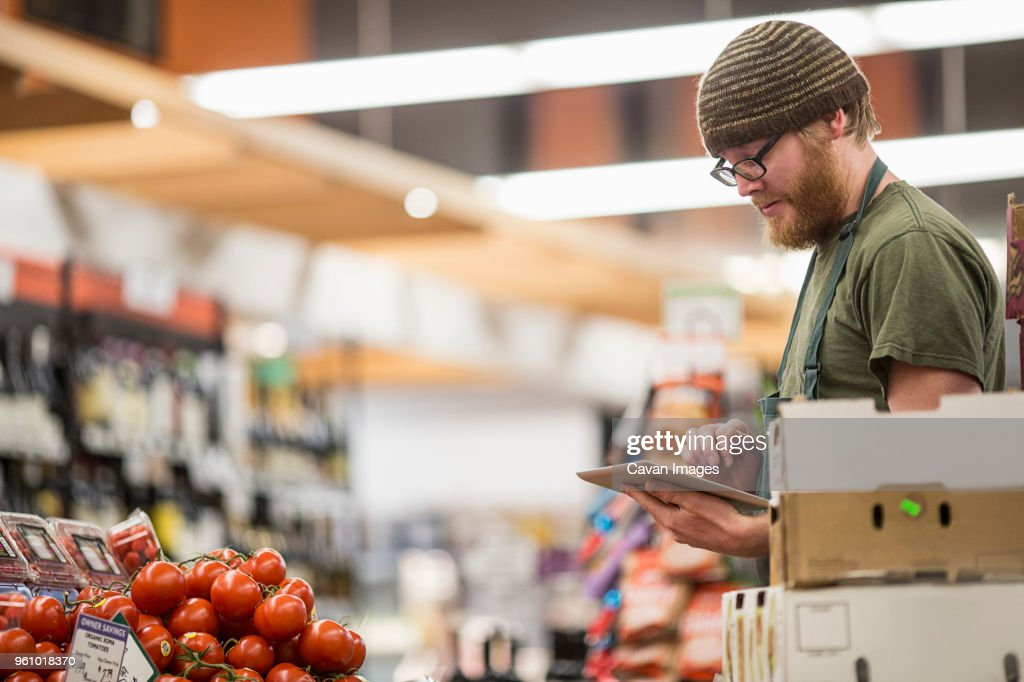 Worker using tablet computer at supermarket : Stock Photo