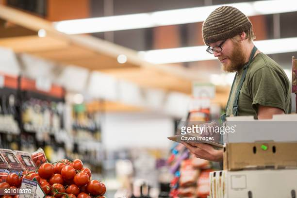 worker using tablet computer at supermarket - cavan images foto e immagini stock