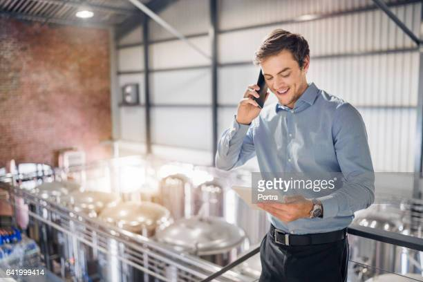 Worker using tablet PC and smart phone in brewery
