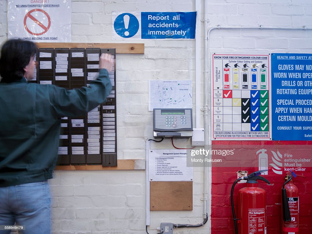 Worker using time clock in factory : Stock Photo