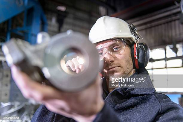 Worker using torch to inspect cast metal parts in foundry