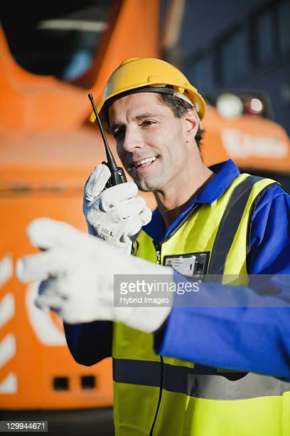 worker using walkie talkie on site - hearing protection stock pictures, royalty-free photos & images