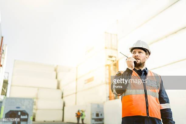 worker using walkie-talkie in commercial dock - dock worker stock photos and pictures