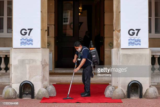 Worker vacuums a red carpet laid out for dignitaries on the first day of the Group of Seven Finance Ministers summit in London, U.K., on Friday, June...