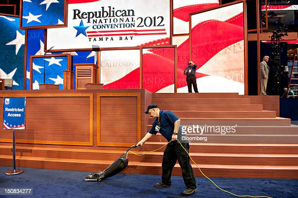 A worker vacuums on the floor of the Republican National Convention in Tampa Florida US on Monday Aug 27 2012 The first day of the RNC is formally...