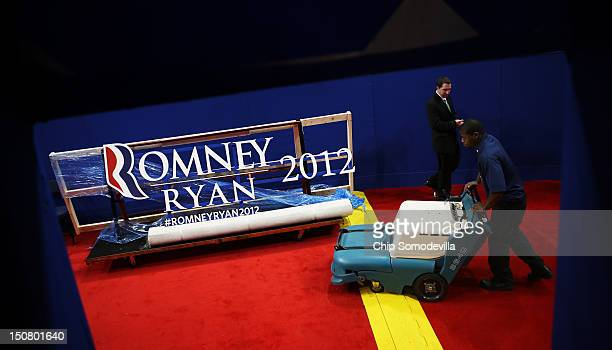A worker vacuums the carpet in front of a campaign sign ahead of the Republican National Convention at the Tampa Bay Times Forum on August 26 2012 in...