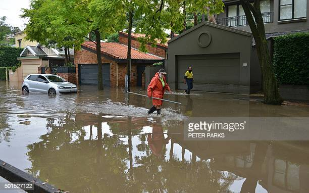A worker wades down a flooded street after a storm in the eastern suburbs of Sydney on December 16 2015 Sydney was smashed by a tornadolike storm...