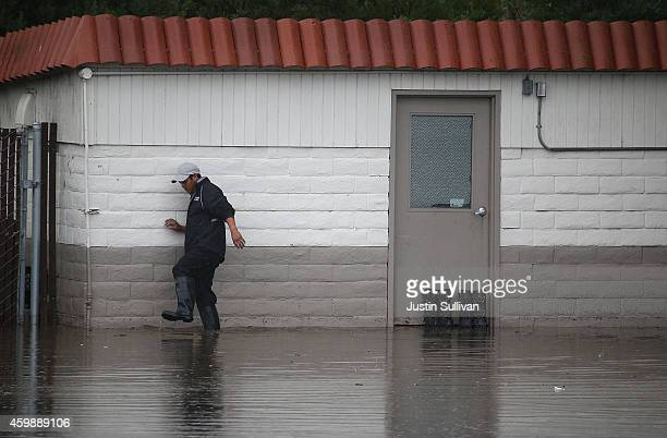 A worker wades through a flooded section of a Chevron gas station on December 3 2014 in Mill Valley California The San Francisco Bay Area is being...