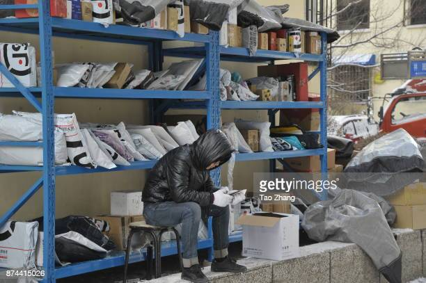A worker waits for students to collect Singles Day shopping parcels as the outdoor temperature reaches minus 15 at a temporary tent in Heilongjiang...