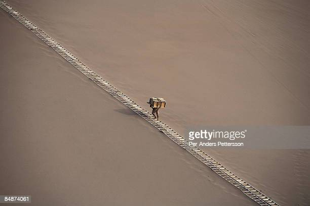 Worker walking on a path in the Gobi desert.