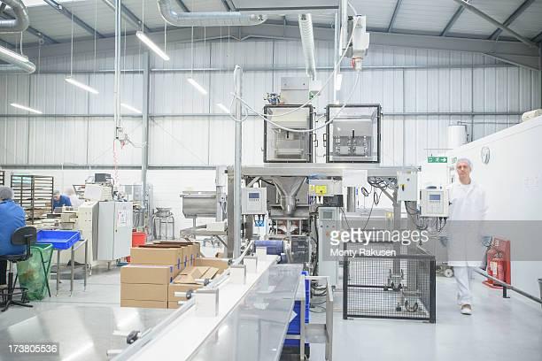 worker walking through packing line in biscuit factory - rechnerunterstützte fertigung stock-fotos und bilder