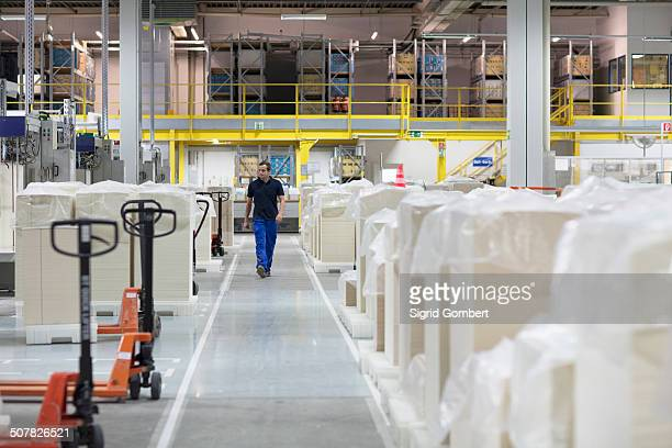 worker walking through paper packaging factory - sigrid gombert stock pictures, royalty-free photos & images