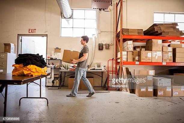 worker walking through warehouse, carrying cardboard box - heshphoto stock-fotos und bilder
