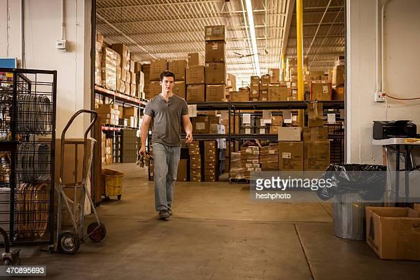 worker walking through warehouse - heshphoto stock-fotos und bilder