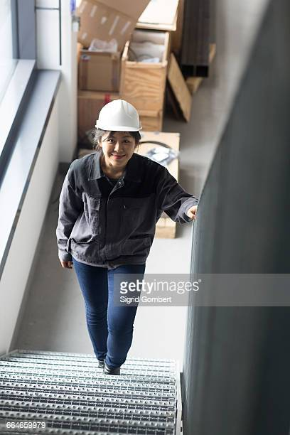 worker walking up staircase in factory - sigrid gombert stock-fotos und bilder
